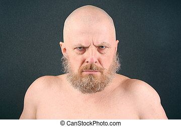 The bearded man of aggressive look negatively looks forward