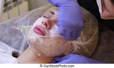 The beautician prepares face girls cream anesthetic before...