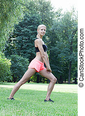 The beautiful blonde stretching outdoors