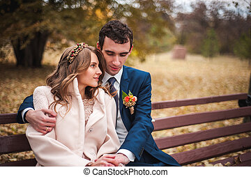 The beautiful bride and handsome groom sitting on a bench in the autumn park