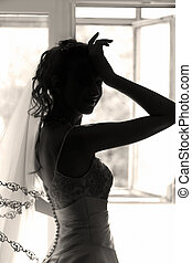 Silhouette - The beautiful bride prepares for wedding. ...