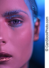 The beautiful face of the girl model with bright blue eyes in a neon shade.