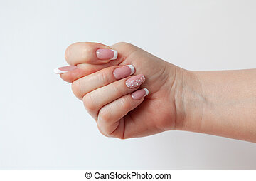 The beautiful female hand with graceful French manicure...