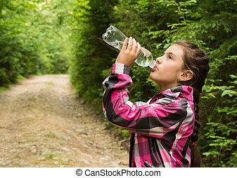 The beautiful girl drinks water
