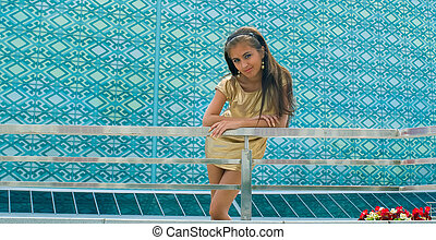 girl in a golden against blue wall