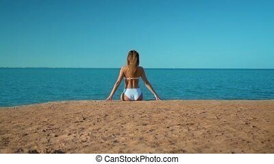 The beautiful girl in a white swimsuit sitting on the background of the sea