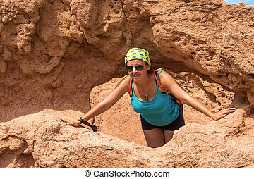 Beautiful girl in the doorway of orange rock canyon Tale, Kyrgyzstan.