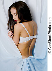 The beautiful girl in underwear a background of a blue fabric