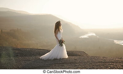 The beautiful girl is walking in the charming modern white dress with wreath of flowers in the mountains in sunset