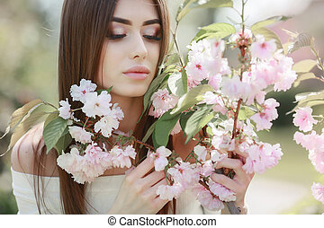 The beautiful girl with a romantic hairstyle and a professional make-up enjoys a smell of pink colors in a garden. The girl dreams. A portrait of the beautiful girl model in the spring in the park.