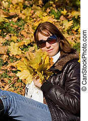 The beautiful girl with autumn leaves