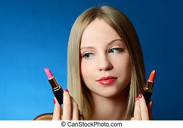The beautiful girl with lipsticks in hands