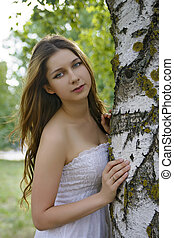 girl with long hair embraces a birch