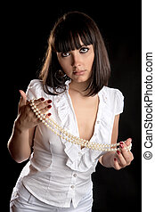 The beautiful girl with pearls on a black