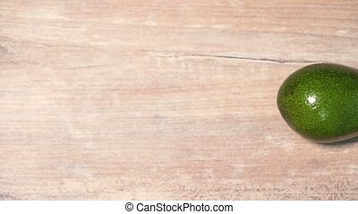 The beautiful green avocados move behind each other on a wooden background. Healthy vegan diet, healthy breakfast 4k