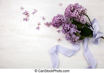 The beautiful lilac on a bright wooden background