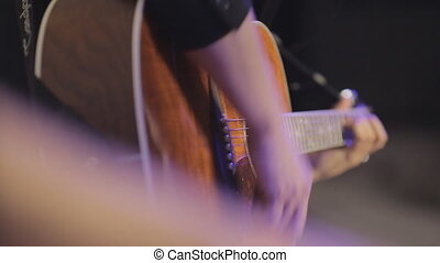 The beautiful man plays the guitar in the club