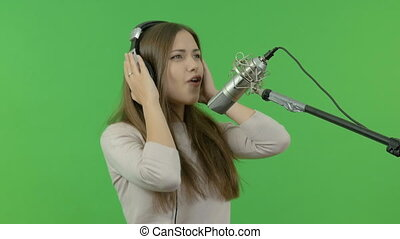 The beautiful singer is very expressive sings in the studio microphone. On a green background.