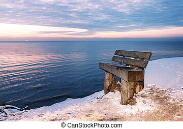 The beautiful winter night at sea stands a lonely bench