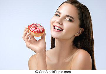 beautiful woman biting a donut