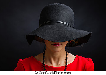 The beautiful woman in a black hat with the wide fields...