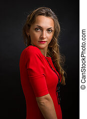 The beautiful woman in a bright dress of scarlet color with...