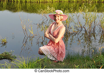 The beautiful woman in a hat smiles, having sat down at a pond.