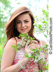 The beautiful woman in flowers of a cherry