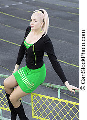the beautiful woman in green sits on a protection of stadium