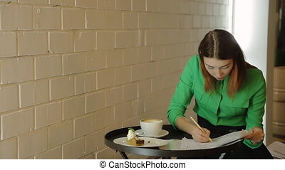 The beautiful woman is sitting in cafe working with the blueprints, drawings correcting plans of buildings