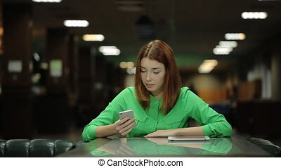 The beautiful woman is waiting for the order working with the cellphone in her hands and smiling.