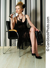 The beautiful woman sits on a chair with a glass in hands.