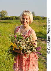The beautiful woman with a bouquet of wild flowers walks in the field.