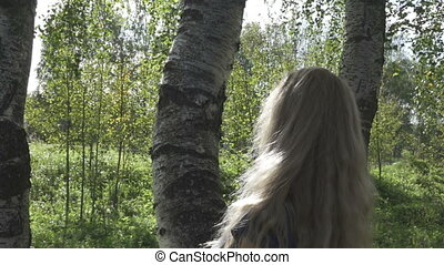 The beautiful woman with smile looks out from birch and waves hair. Slow motion