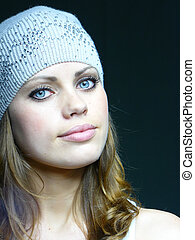 beautiful young blue-eyed girl in a grey cap with pastes