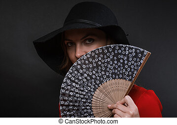 The beautiful young woman in a black wide-brimmed hat and...