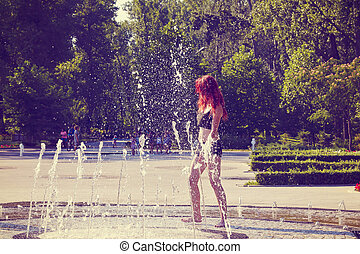 The beautiful young woman is playing at a fountain