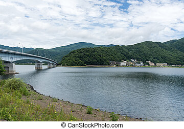 The beauty of the forest mountains above the lake in Japan. Pier on the beach