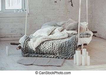 The bed suspended from the ceiling. Grey big cozy blanket...