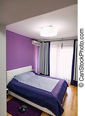 The bedroom in the apartment. Bed, wardrobe, bedside tables in t