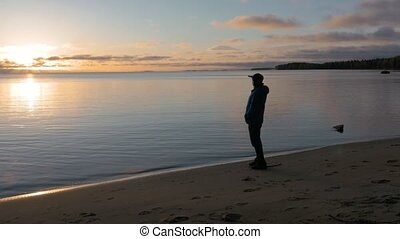 A man meets the dawn on the shore of a beautiful lake. He...