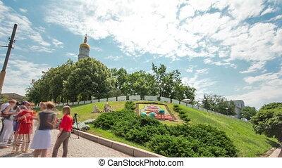 The bell tower of the Assumption Cathedral Uspenskiy Sobor timelapse hyperlapse with flowerbed, Kharkov, Ukraine.