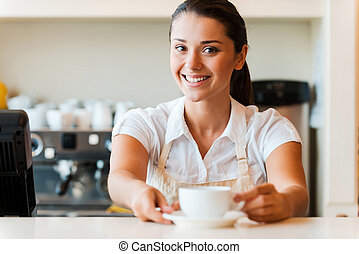 The best coffee in town for you. Beautiful young woman in apron serving coffee and smiling while standing in coffee shop