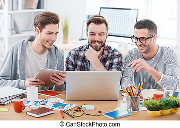 The best decisions with good mood. Three young happy men working together while sitting at their working place in office