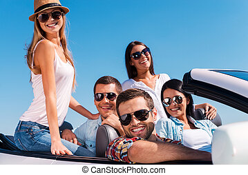 The best friends ever. Group of young happy people enjoying road trip in their white convertible