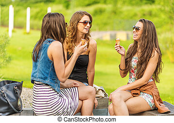 The best friends. Three beautiful woman eating ice cream in the City
