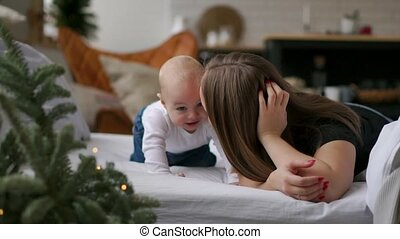The best moments from life, a loving happy young mother hugs a nursing son, on a snow-white blanket, on a white background. concept of love, family, and happiness Concept: children, kids, baby, babies