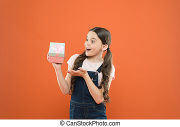 The best present ever. Small child holding birthday present on orange background. Little girl with wrapped present box. Surprised kid receiving present on boxing day