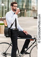 The best way to start a day. Side view of handsome young businessman drinking coffee while sitting on his bicycle