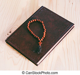 the Bible and wooden rosary on the table, top view closeup